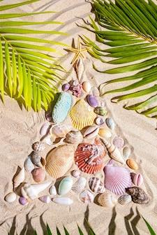 Weihnachtsstrandhintergrund mit einer kreativen anordnung für die muscheln, die einen weihnachtsbaum auf dem strukturierten sand bilden