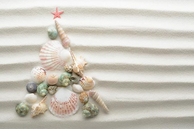 Weihnachtsstrandhintergrund. weihnachtsbaum mit muscheln gemacht