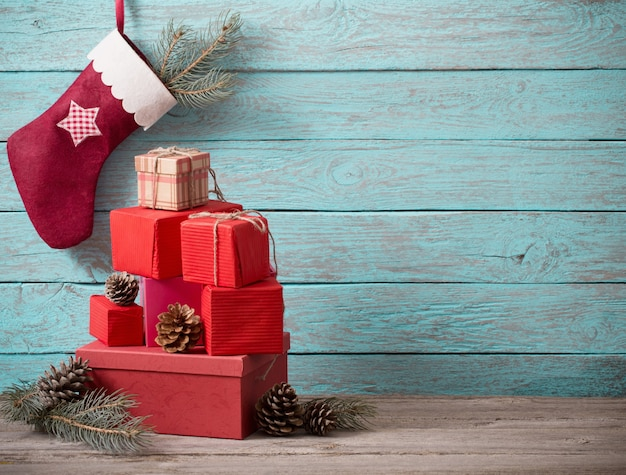 Weihnachtsstrumpf mit geschenken auf holzwand