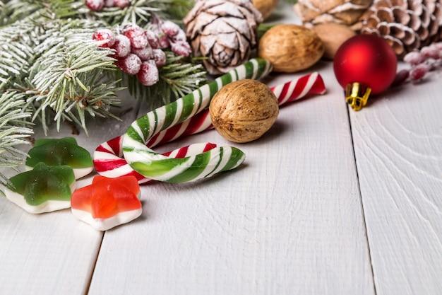 Weihnachtssüßigkeiten und tannenzweige mit tannenzapfen