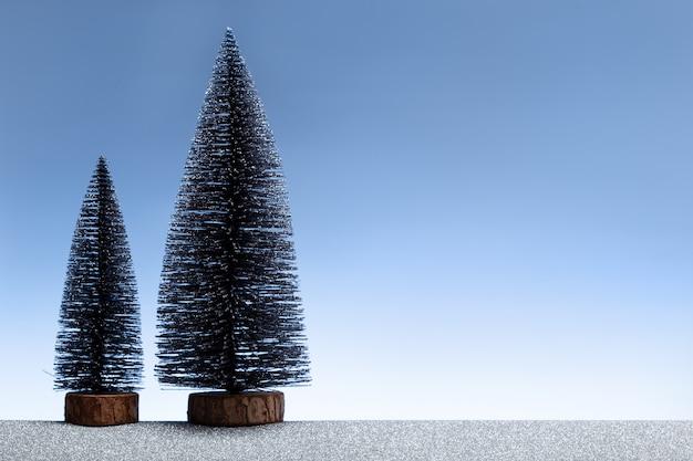 Weihnachtsszene mit miniaturtannenbäumen und funkelndem silbernem boden