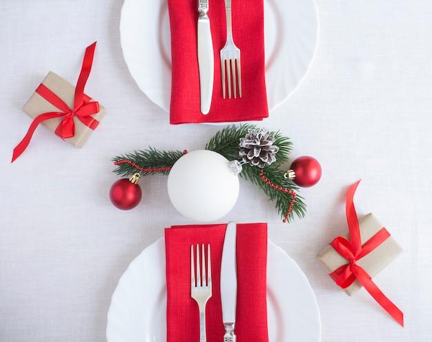 Weihnachtstabelleneinstellung auf der weißen tischdecke. ansicht von oben. nahaufnahme.