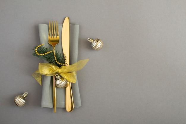 Weihnachtstabelleneinstellung mit grauer serviette auf dem grauen hintergrund. ansicht von oben. platz kopieren.
