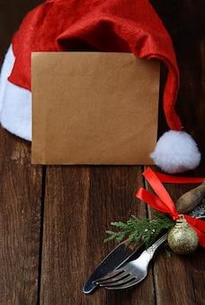 Weihnachtstabellengedeck, leeres papier und santa claus-hut