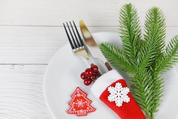 Weihnachtstabellengedeckdekoration mit gabelmesser in weihnachtsmann-hut und in der kiefer auf festlichen weihnachtsabendessenfeiertagen des weißen plattenweihnachtsneujahrsfutter-mittagessens