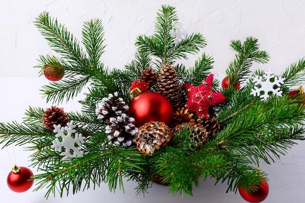 Weihnachtstabellenmittelstück mit roten bällen und handverzierten kiefernkegeln