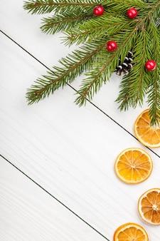 Weihnachtstanne dekoriert und geschnittene getrocknete orangen auf hellem holzhintergrund