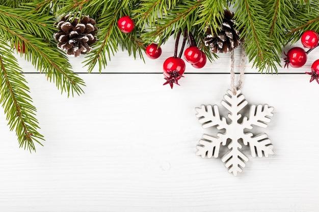 Weihnachtstanne verzierte und dekorative schneeflocke auf hellem hölzernem hintergrund