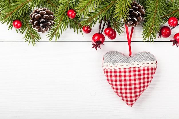 Weihnachtstanne verziertes und dekoratives herz auf hellem hölzernem hintergrund