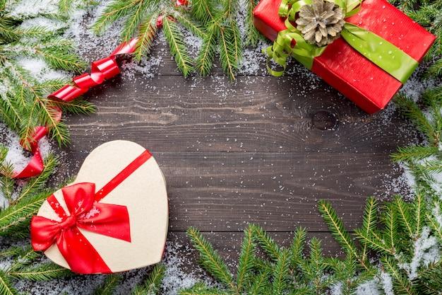 Weihnachtstannenbäume im schnee mit geschenken auf einem dunklen hölzernen brett