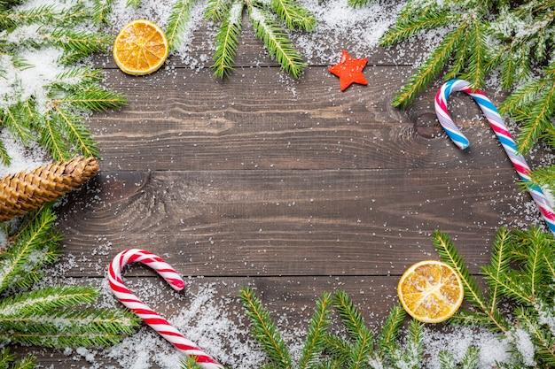 Weihnachtstannenbäume im schnee mit kegel, zuckerstangen, dekorativem stern und getrockneten orangen auf einem dunklen hölzernen brett