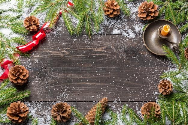 Weihnachtstannenbäume im schnee mit kegeln, rotem band und kerze im kerzenständer auf einem dunklen hölzernen brett. kopieren sie platz für ihren text.