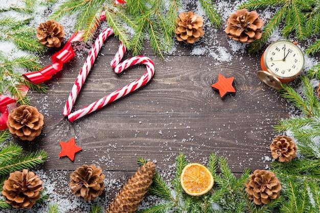 Weihnachtstannenbäume im schnee mit kegeln, zuckerstangen, weinleseuhr
