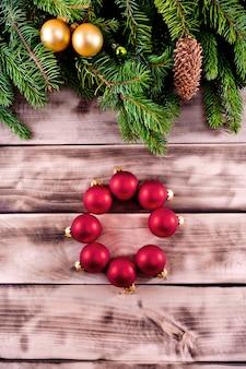 Weihnachtstannenbaum auf natürlichem hölzernem hintergrund mit roten bällen.