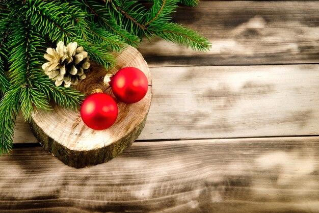 Weihnachtstannenbaum auf naturholz mit kiefernkegel und roten bällen.