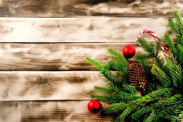 Weihnachtstannenbaum auf naturholz mit süßigkeit und roten bällen.