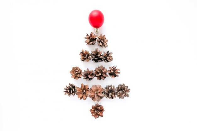 Weihnachtstannenbaum gemacht von den kiefernkegeln und vom redball auf weißem hintergrund.