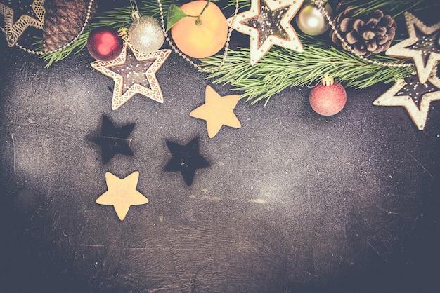 Weihnachtstannenbaum mit dekoration auf dunklem holzbrett, lebkuchenplätzchensterne. speicherplatz kopieren.