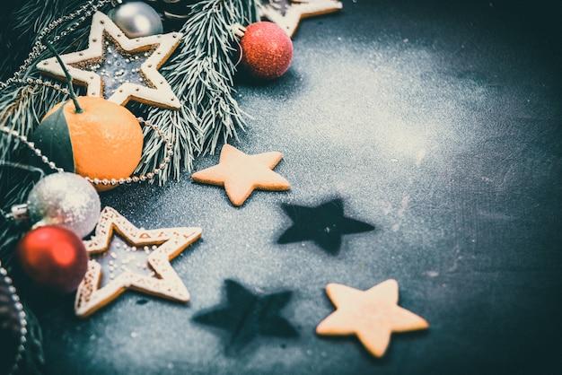 Weihnachtstannenbaum mit dekoration auf dunklem holzbrett, lebkuchenplätzchensterne