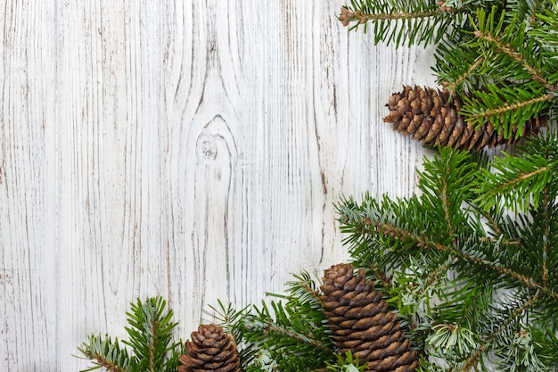 Weihnachtstannenbaum mit kiefernkegeln auf einem hölzernen brett