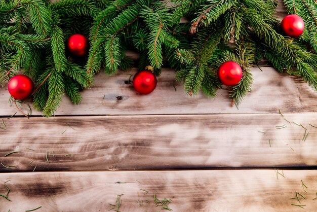 Weihnachtstannenbaum mit roten bällen auf naturholz