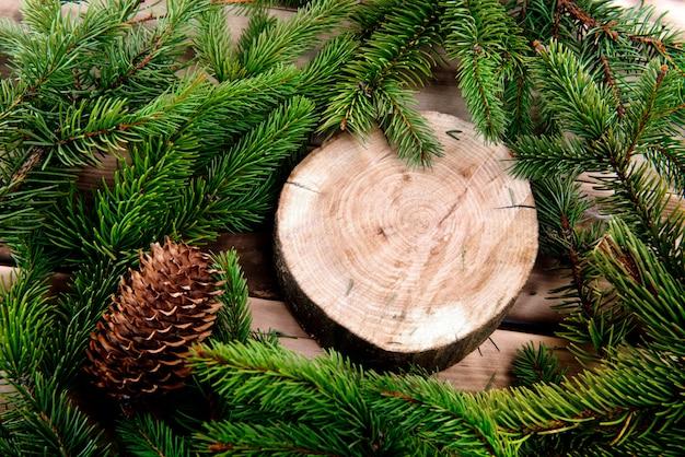 Weihnachtstannenbaum und runder hölzerner schnitt auf naturholz