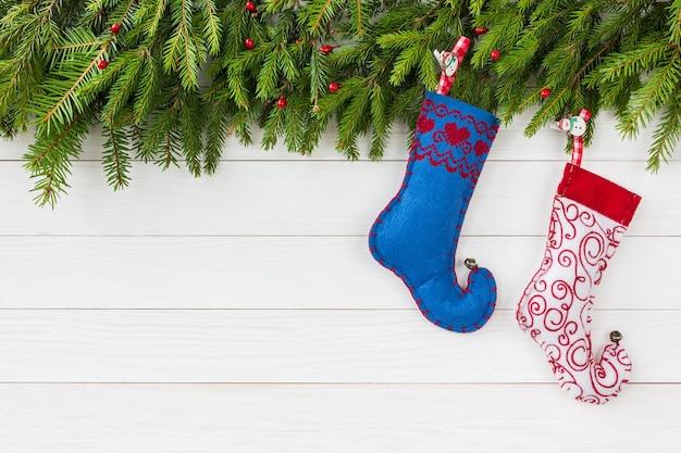Weihnachtstannenbaum und weihnachtssocken auf weißem holz