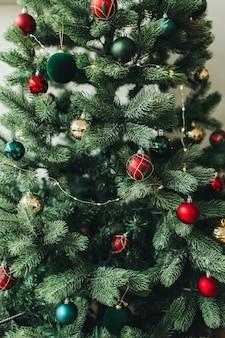 Weihnachtstannenbaum verziert mit wunderschönen roten, goldenen, grünen spielzeugen, bällen und girlanden