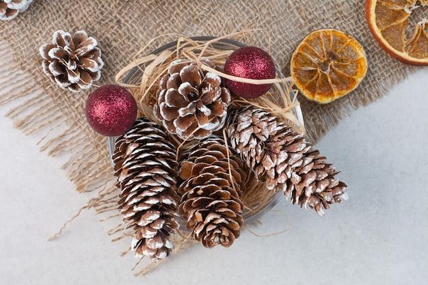 Weihnachtstannenzapfen mit getrockneten orangen auf sackleinen. hochwertiges foto