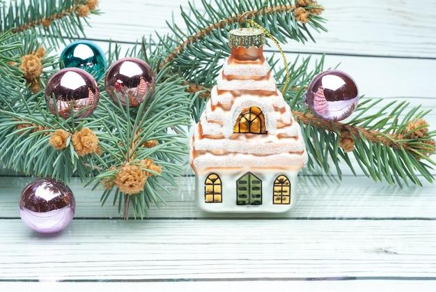 Weihnachtstannenzweig mit dekoration auf weißem holzbretthintergrund