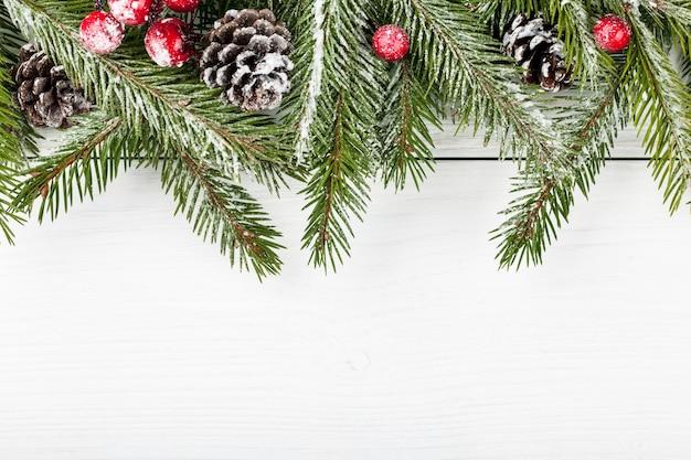 Weihnachtstannenzweig mit tannenzapfen und roten beeren auf hellem holzhintergrund