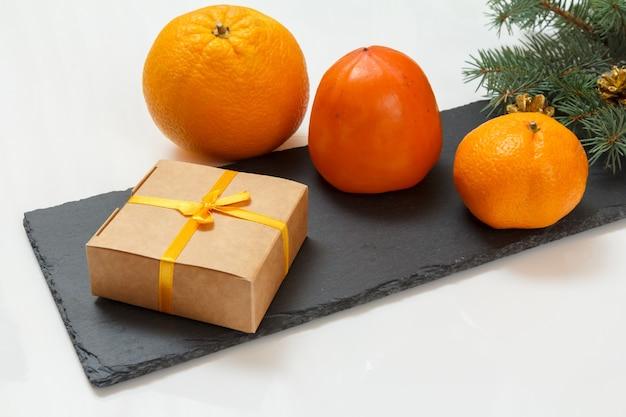 Weihnachtstannenzweig mit zapfen, einer geschenkbox, einer orange, einer mandarine und einer kaki auf dem steinbrett und dem weißen hintergrund