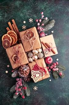 Weihnachtstannenzweige, weihnachtskugeln, geschenkbox, holzschneeflocken und sterne auf grünem betonsteinhintergrund für ihre weihnachtsgrüße. draufsicht mit kopienraum. weihnachtsgrußkarte.