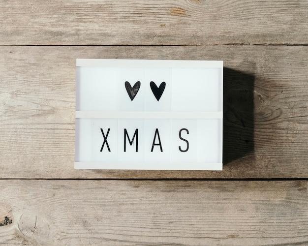 Weihnachtstext in led-tafel mit hölzernem hintergrund