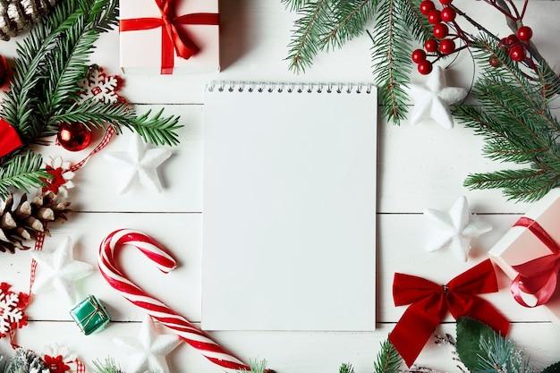 Weihnachtsthema mit leerem papier auf weißem hölzernem hintergrund. weihnachtsdekoration.