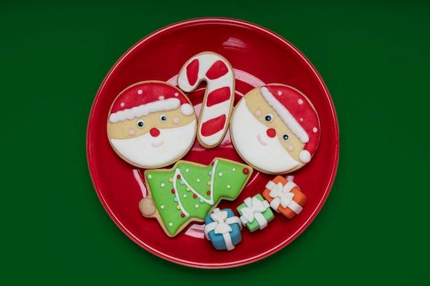 Weihnachtsthema mit zucker überzogene kekse auf einem leuchtend roten teller.