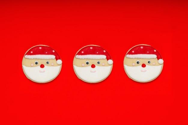 Weihnachtsthema zuckerbeschichtete kekse auf einem leuchtend roten hintergrund.