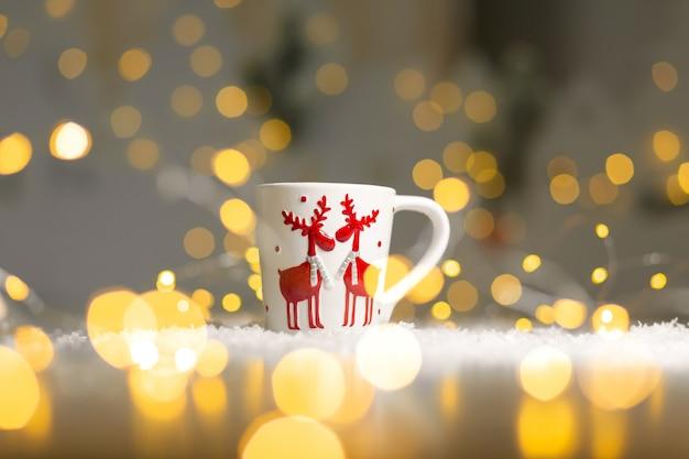 Weihnachtsthematischer becher mit rotwild. gemütliche warme familiäre atmosphäre, festliche einrichtung