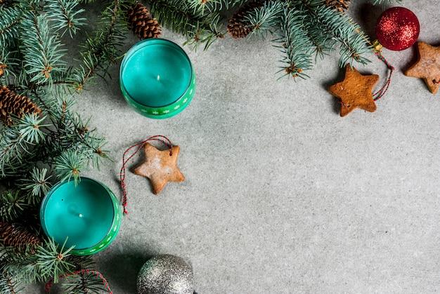 Weihnachtstisch, für grußkarte. weihnachtsdekoration, kerzen, tannenbaum und lebkuchenplätzchen auf grauer steintabelle. ansicht von oben.