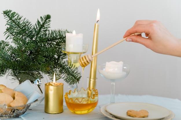 Weihnachtstisch mit goldenen kerzen, honig und kiefer. hochwertiges foto