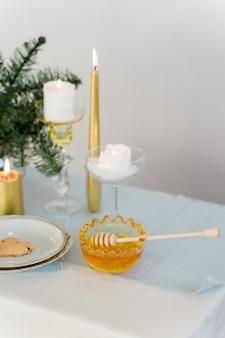 Weihnachtstisch mit goldenen kerzen, honig und kiefer