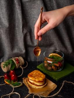 Weihnachtstisch mit löffel, honig und pfannkuchen