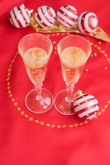 Weihnachtstisch mit rotem tuch und dekoration mit zwei gläsern champagner