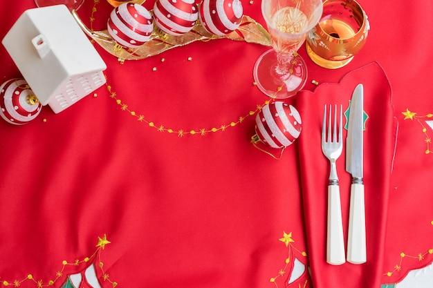 Weihnachtstisch mit rotem tuch und weihnachtsschmuck, messer und gabel, gläser champagner