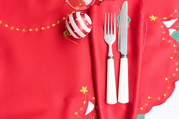 Weihnachtstisch mit rotem tuch, weihnachtsschmuck, messer und gabel