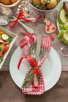 Weihnachtstisch mit teller, besteck. weihnachtsfeiertag-hintergrund. tabelleneinstellung für den urlaub.