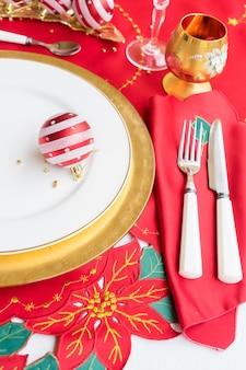 Weihnachtstisch mit weiß-goldenem teller, messer und gabel