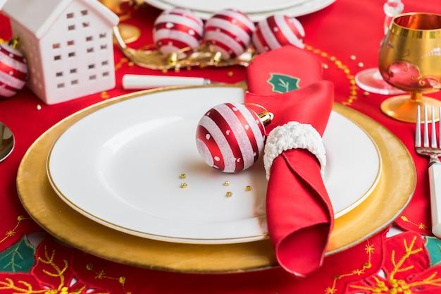 Weihnachtstisch mit weiß-goldenem teller und weihnachtsdekoration zum abendessen serviert