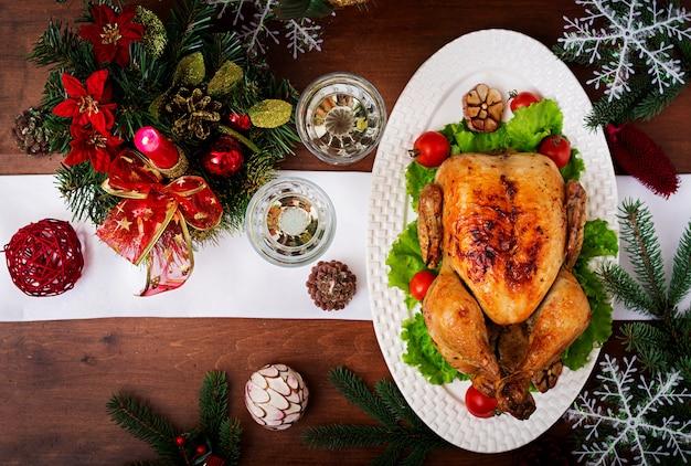 Weihnachtstisch serviert mit einem truthahn, dekoriert mit hellem lametta und kerzen