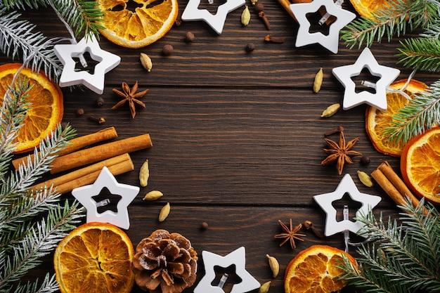 Weihnachtstisch. tannenzweige mit getrockneten gewürzen aus orange, kardamom und glühwein, auf einen dunklen holztisch gestreut. platz für ihren text.